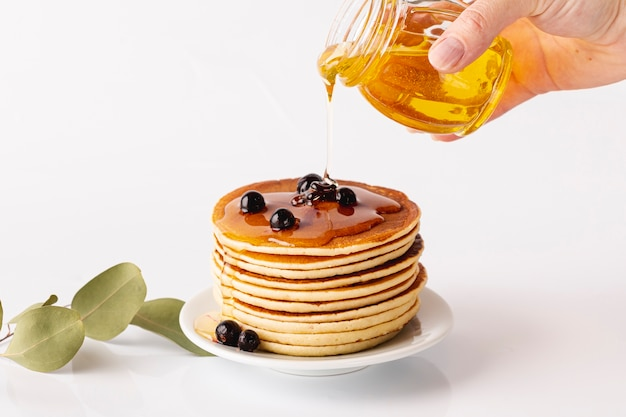 Honey poured over pancake tower on plate with blueberries
