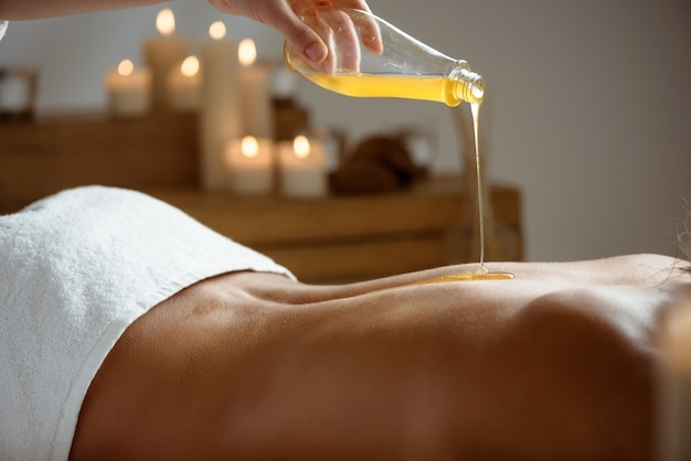 Honey pouring on woman's naked back in spa salon.