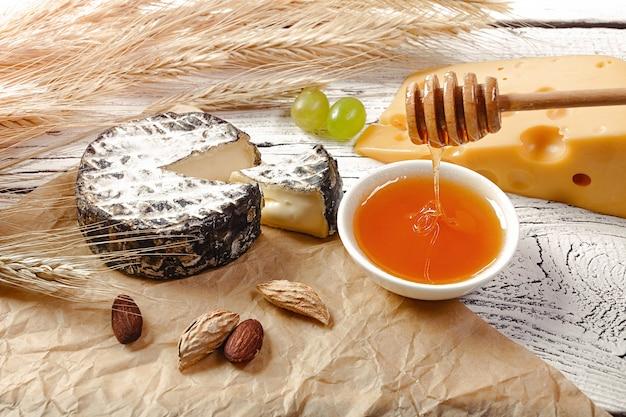 はちみつは、しわくちゃの紙と白い木製の背景にチーズ、ナッツ、小麦の穂の近くのボウルに注ぐ。