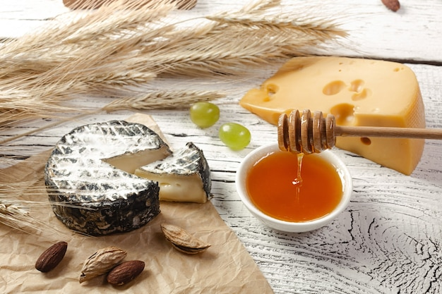 Honey pours into a bowl near cheese, nuts and ears of wheat on crumpled paper and white wooden background.