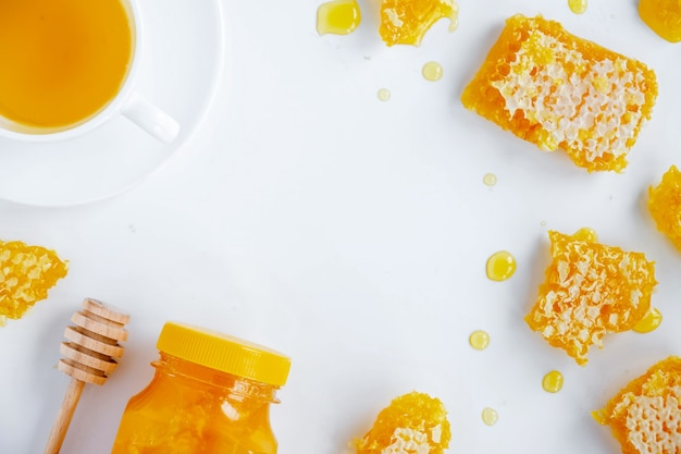 Состав медовых продуктов. мед в банке, соты, чай и специальная ложка. белый фон