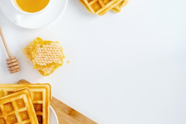 Состав медовых продуктов. соты, вафли, чай и специальная ложка. белый фон