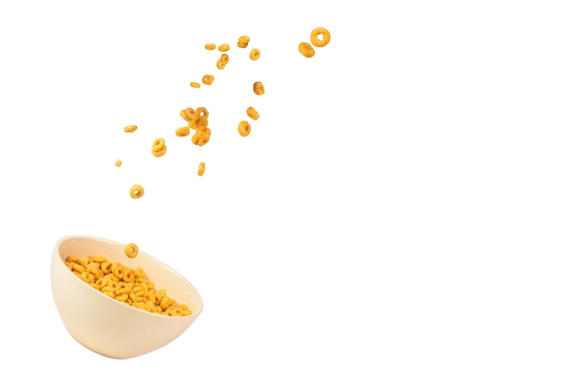 Honey rings cereal box for morning breakfast. corn flakes falling to the white bowl. motion. copyspace.