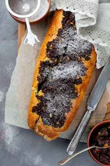 Honey roll with poppy seeds and raisins on a gray concrete background