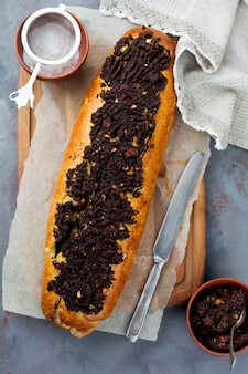 Honey roll with poppy seeds and raisins on a gray concrete surface
