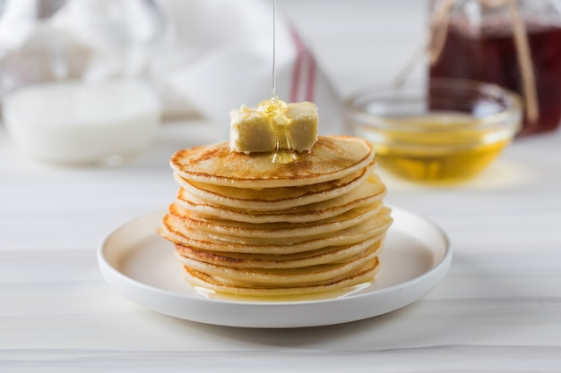 Honey sauce pours over a stack of pancakes breakfast concept