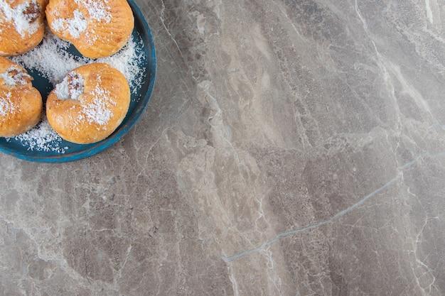 Frollini al miele con scaglie di cocco su un piatto di legno su marmo.
