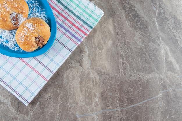 Frollini al miele su un piatto di legno su un canovaccio su marmo.