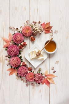 Honey, soft cheese and figs on white wooden background surrounded by floral pattern of pink flowers and leaves.