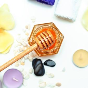 Медовое санаторно-курортное лечение. золотой мед в баночке, цветы орхидеи, полотенца и ароматические свечи. натуральный домашний уход за кожей. плоская планировка, вид сверху.