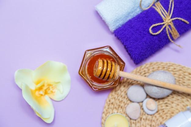 Медовое санаторно-курортное лечение. золотой мед в баночке, цветы орхидеи, полотенца и ароматические свечи. натуральный домашний уход за кожей. сиреневый фон, вид сверху.