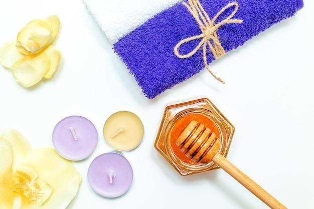 Медовое санаторно-курортное лечение. золотой мед в баночке, цветы орхидеи, полотенца и ароматические свечи. натуральный домашний уход за кожей. белый фон, вид сверху.