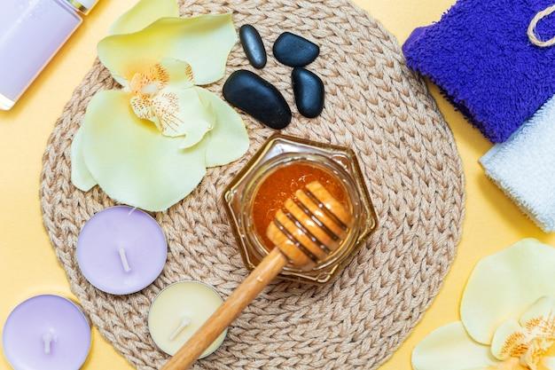 ハニースパトリートメント。瓶の中の金の蜂蜜、蘭の花、タオル、香りのキャンドル。自然な家庭用スキンケア。黄色の背景、上面図。セレクティブフォーカス
