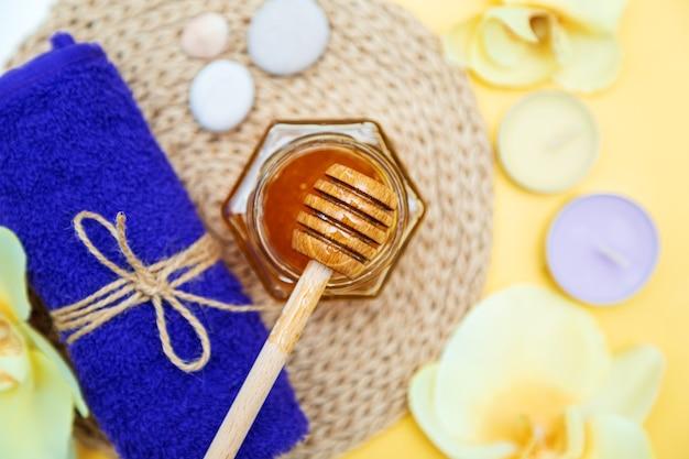 ハニースパトリートメント。瓶の中の金の蜂蜜、蘭の花、タオル、香りのキャンドル。自然な家庭用スキンケア。黄色の背景、上面図。