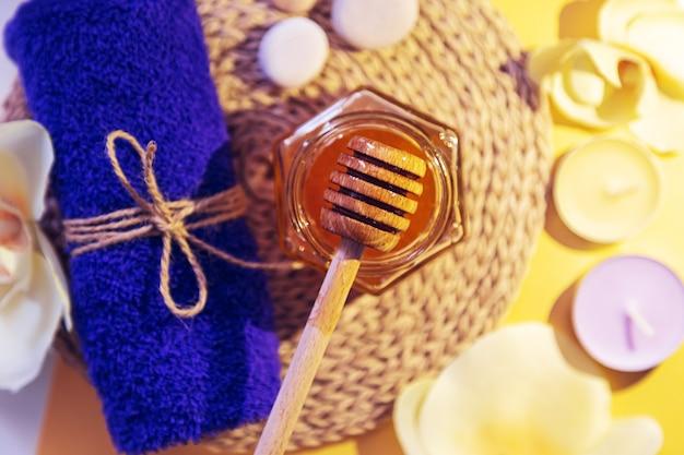 Медовое санаторно-курортное лечение. золотой мед в баночке, цветы орхидеи, полотенца и ароматические свечи. натуральный домашний уход за кожей. желтый фон, вид сверху.