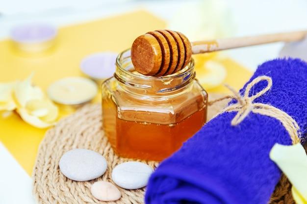 Медовое санаторно-курортное лечение. золотой мед в баночке, цветы орхидеи, полотенца и ароматические свечи. натуральный домашний уход за кожей. желтый фон.