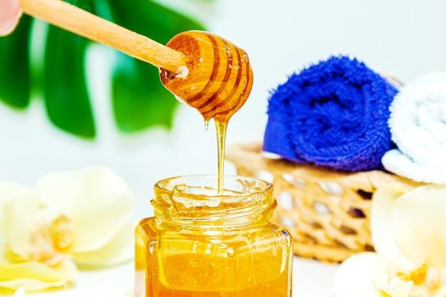 ハニースパトリートメント。瓶の中の金の蜂蜜、蘭の花、タオル、香りのキャンドル。自然な家庭用スキンケア。