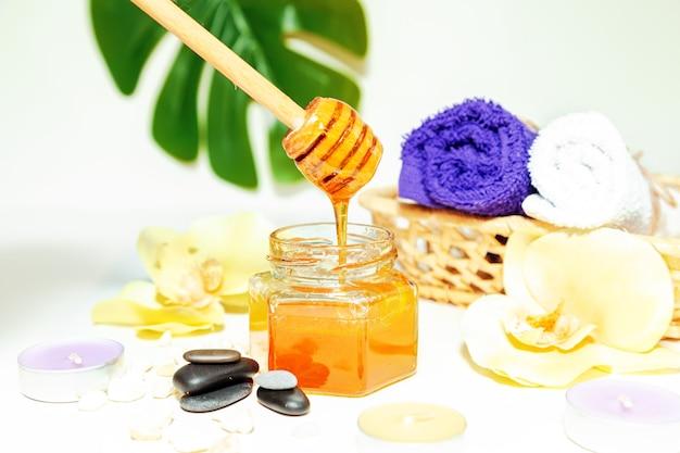 Медовое санаторно-курортное лечение. золотой мед в баночке, цветы орхидеи, полотенца и ароматические свечи. натуральный домашний уход за кожей.