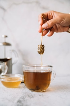 Honey stick above a cup of tea being held in hand