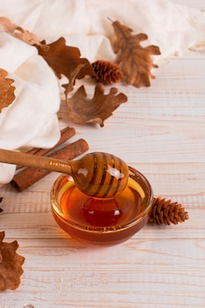 Honey, stick, jar, scarf, dry leaves. rustic sweet autumn photo, white wooden background, copyspace.