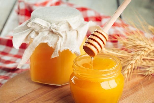 Медовый . сладкий мед в стеклянной банке на деревянных фоне.