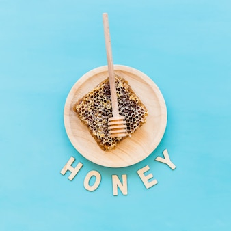 Honey text with honeycomb and dipper on wooden plate over the blue background