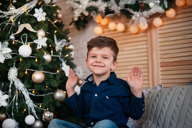 여보, 어린 소년은 크리스마스 트리 근처에 앉아서 웃는다. 잔치를 기다리는 아기