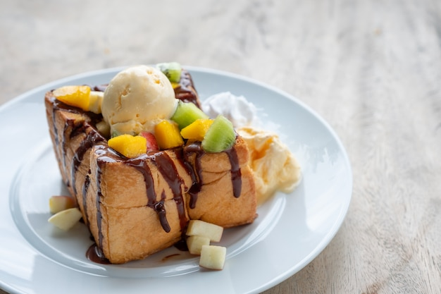Honey toast ice cream vanilla with sliced fruits and chocolate sauce