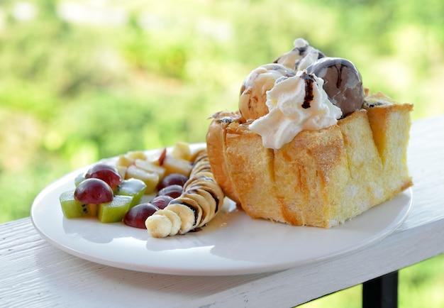 Honey toast and ice cream on white dish wood table