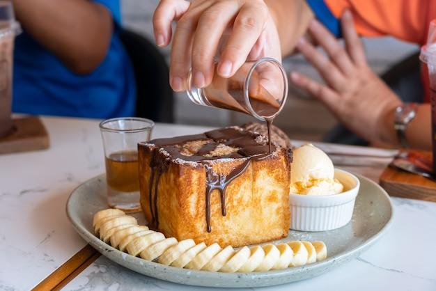 Медовый тост с нарезанным бананом, ванилью и шоколадным мороженым на белом мраморном столе. женщина рука наливает шоколадный соус на медовый тост
