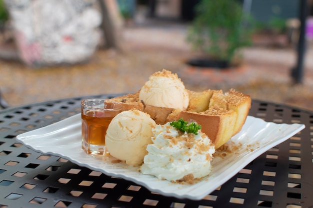 The honey toast on the table, the side dish is ice cream, honey, whipping cream, and sprinkled with crushed nuts.