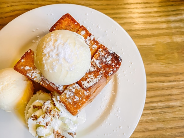 Honey toast with vanilla ice-cream on top and whipped cream served on the table