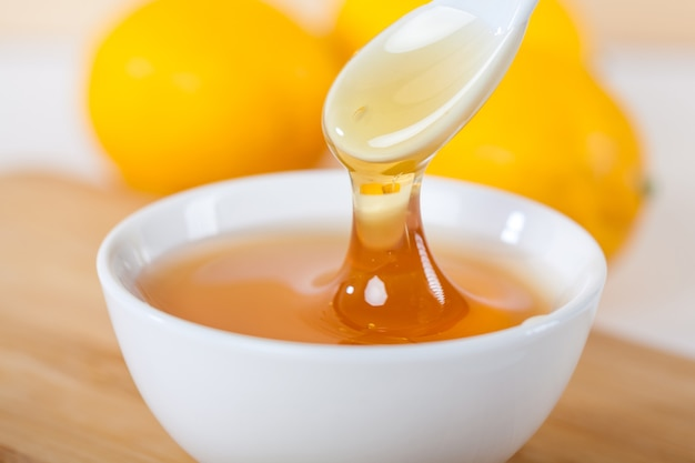 Honey in a white ceramic bowl with spoon and lemon on a wooden kitchen board.