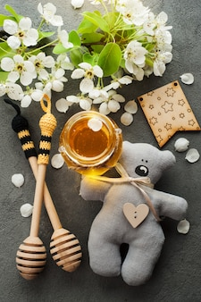 Honey with blossoms and wooden spoons