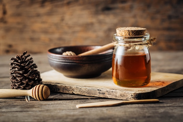 Honey with dipper on wooden background