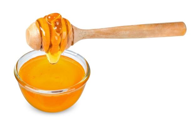 유리 그릇과 나무 숟가락 흰색 배경에 고립 된 꿀