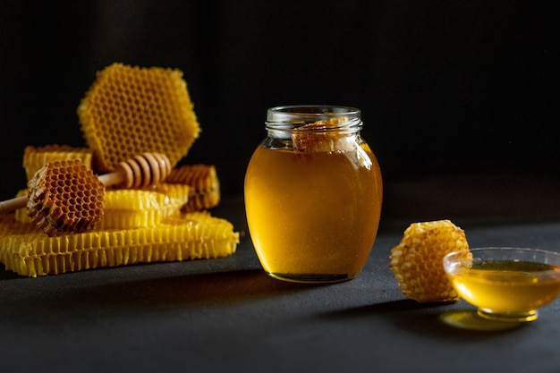 Honey with honeycomb on black table