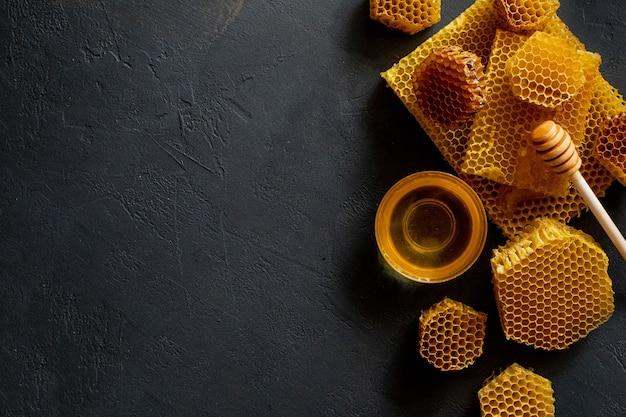 검은 테이블에 벌집이 있는 꿀, 위쪽 전망. 텍스트를 위한 공간입니다.