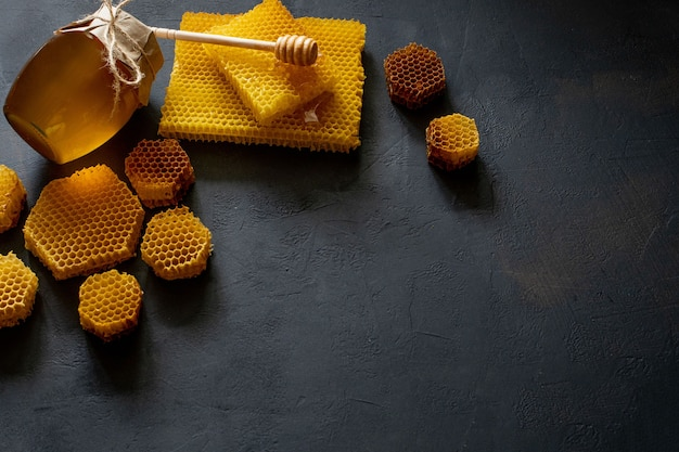 Мед с сотами на черном столе, вид сверху. место для текста.