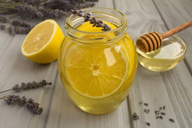 Мед с лимоном и лавандой в стеклянной банке на сером деревянном столе