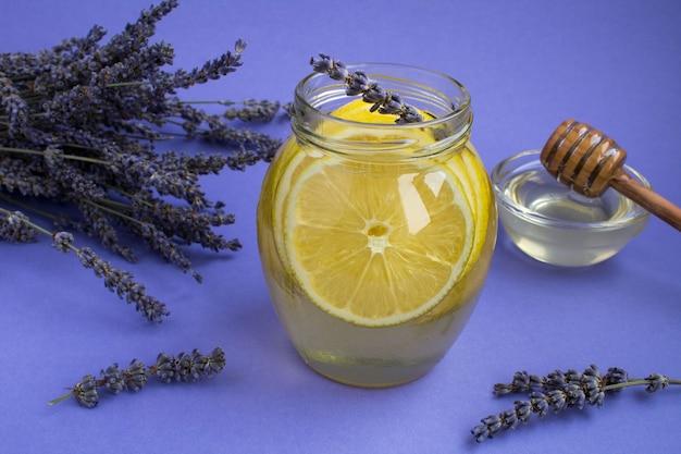 紫の背景のガラスの瓶にレモンとラベンダーと蜂蜜