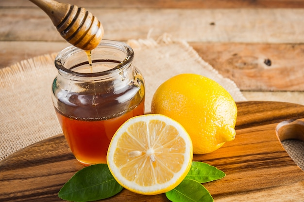 Honey with lemon on background