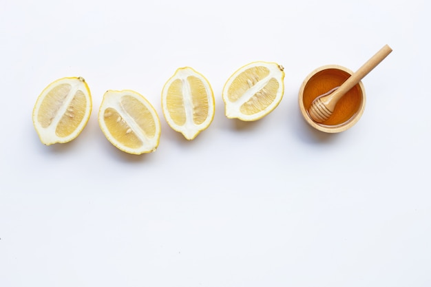 Honey with lemon on white background. copy space