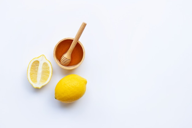 Honey with lemon on white background
