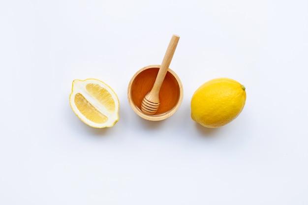 Honey with lemon on white background