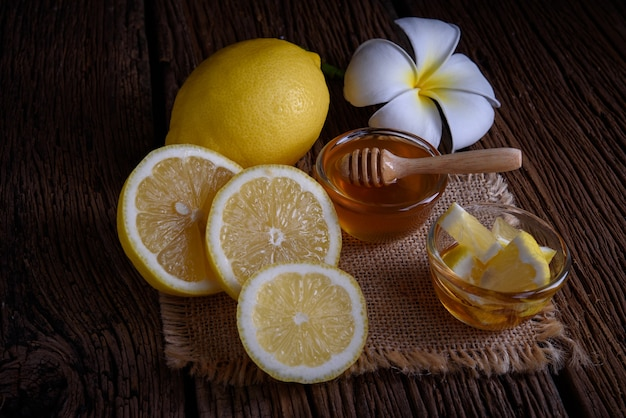 Honey with lemons on wooden table.