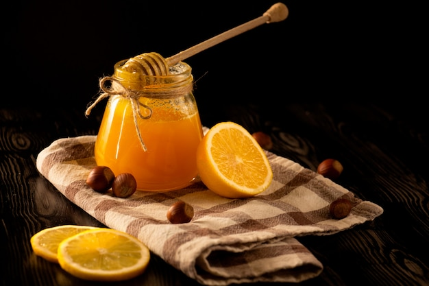 Honey with nuts, lemon and a spoon for honey on a checked tablecloth with black background