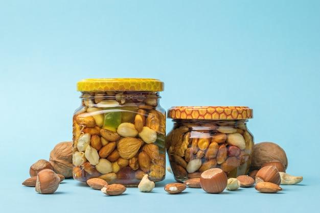파란색 배경에 유리 항아리에 다양한 종류의 견과류와 꿀.