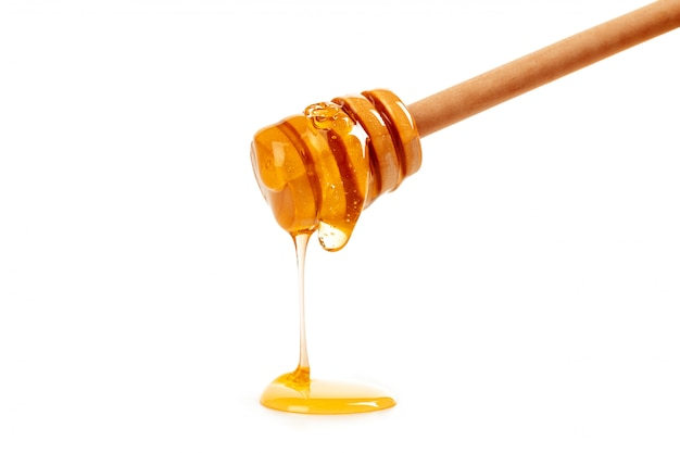 Honey with wooden drizzler isolated on white