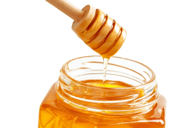 Honey with wooden drizzler isolated